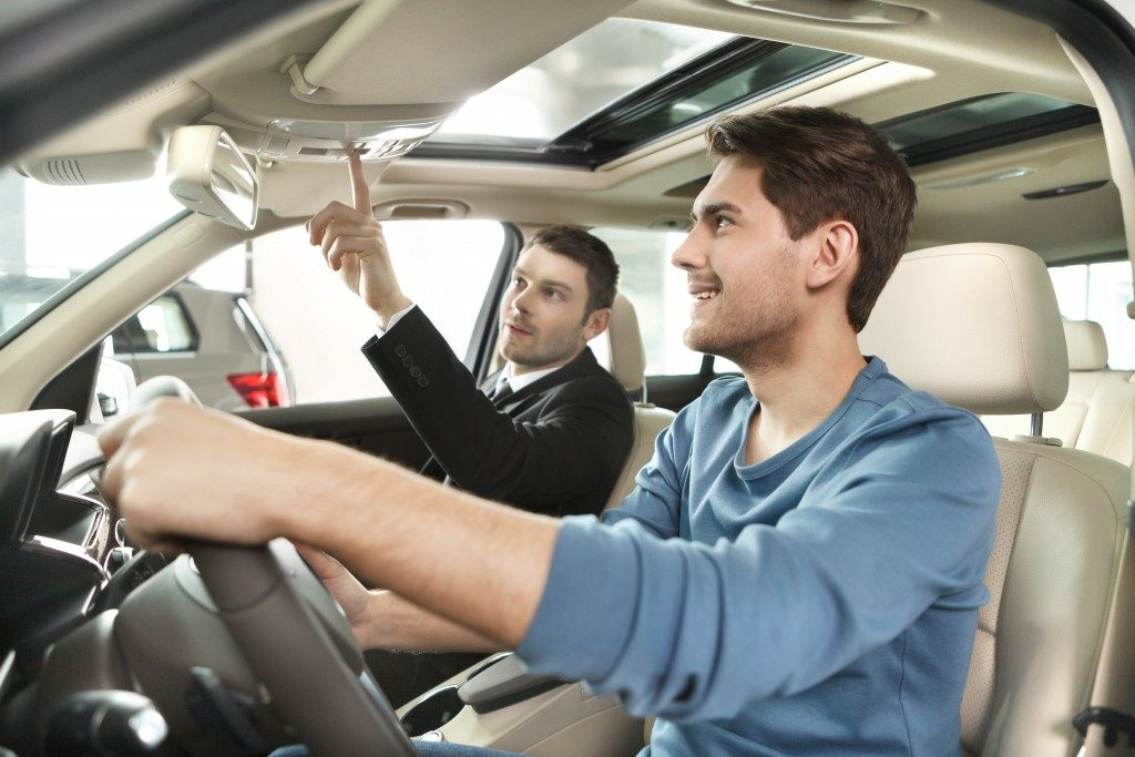 man and sales agent sitting inside a car