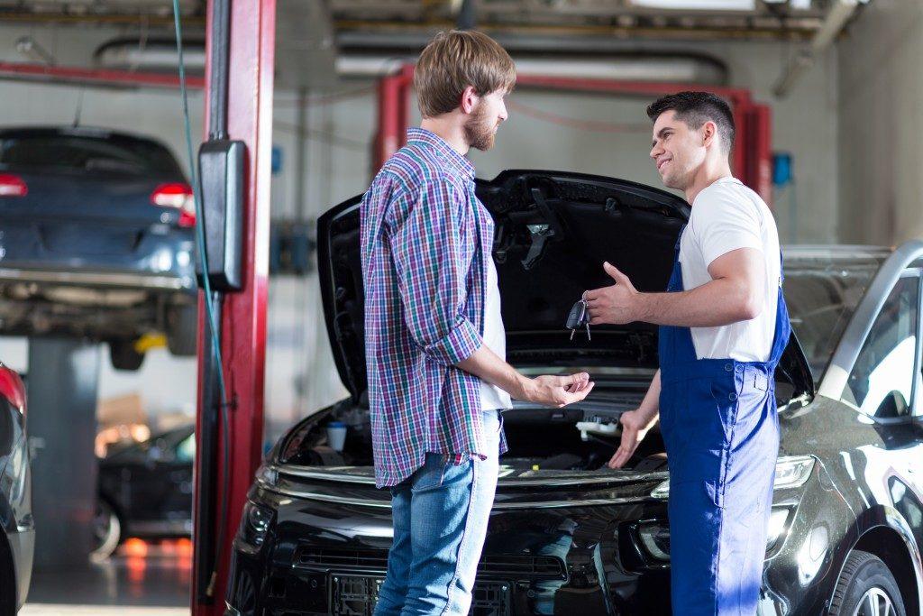Car repair man handing client's car keys