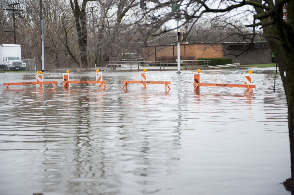 Flooded transportation sign with road barriers