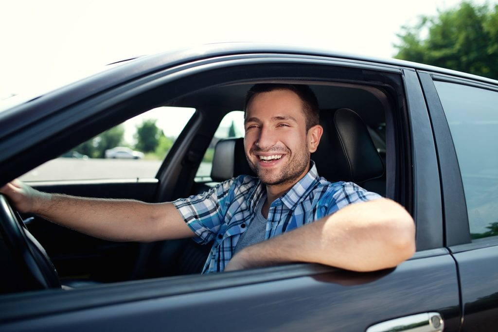 man smiling while driving a car