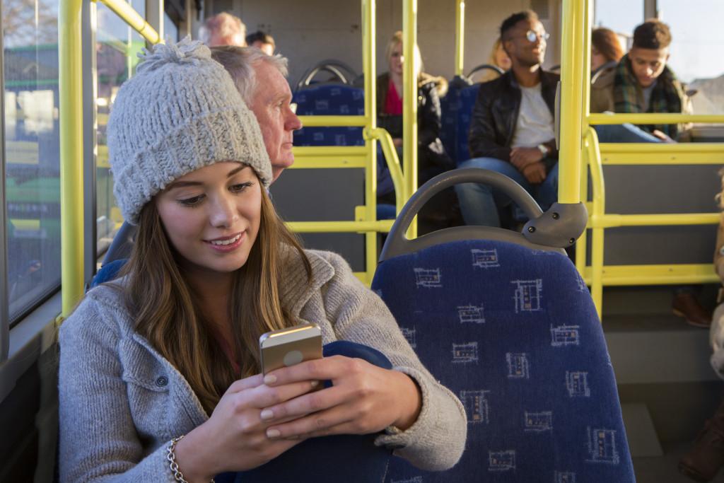 woman using her smart phone on public transportation